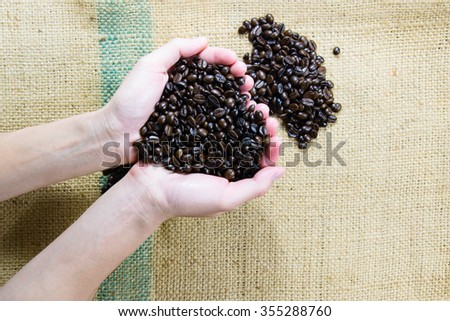 Roasted coffee beans in hand over  the linen fabric - stock photo