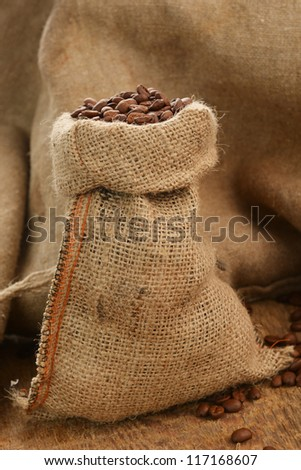 Roasted coffee beans in jute sack on wooden background