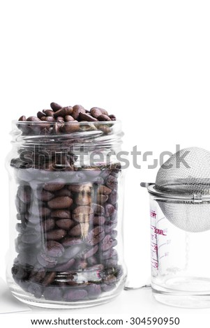 roasted coffee beans in retro glass jar with coffee shot glass and strainer - stock photo