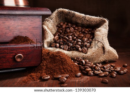 Roasted coffee beans in sack, with old vintage coffee grinder with ground coffee on wooden background. Traditional dark brown coffee still life.