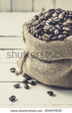 Roasted coffee beans in sackcloth bag on wooden background, vintage style - stock photo