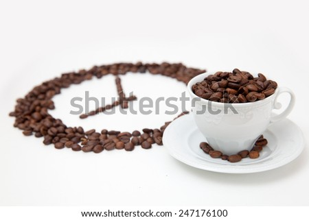 Roasted coffee beans in shape of clock and white cup - stock photo