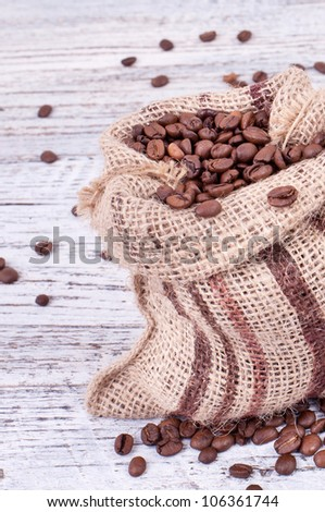 roasted coffee beans in the bag on a wooden board