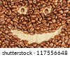 Roasted coffee beans in the form of a smiling face background - stock photo