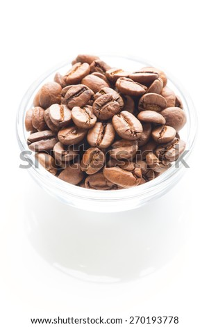 Roasted coffee beans in the glass bowl isolated - stock photo