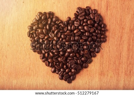 Roasted coffee beans in the shape of the heart in soft tone sun flare.