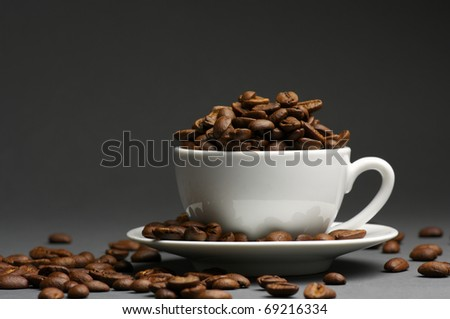 Roasted coffee beans in white cup with saucer on dark gray background.