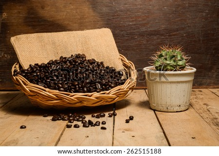 roasted coffee beans in wicker basket, with cactus - stock photo