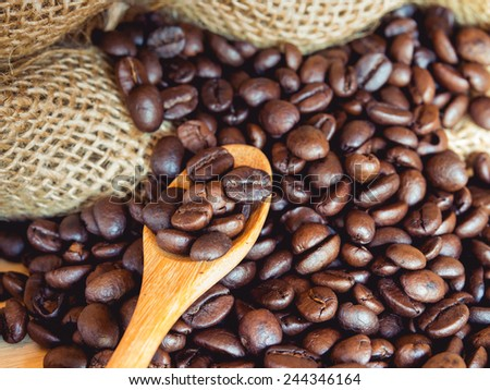 Roasted coffee beans in wooden spoon on roasted coffee beans background. : Vintage style and filtered process - stock photo