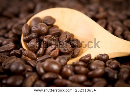 roasted coffee beans in wooden spoon placed on coffee beans as background , selective focus - stock photo