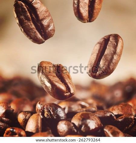 roasted coffee beans is falling down, warm colors toned - stock photo