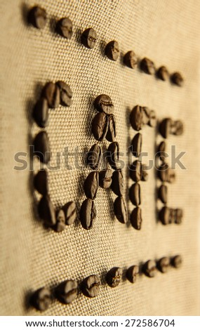 """Roasted coffee beans making the word """"CAFE"""" on the burlap background. - stock photo"""