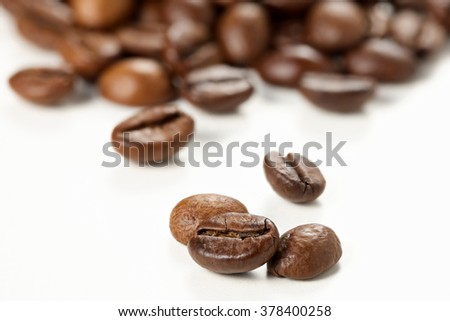 Roasted coffee beans on a white background, selective focus.