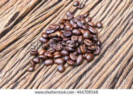 Roasted coffee beans on a wood floor.