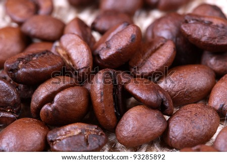 Roasted coffee beans on linen sackcloth - stock photo