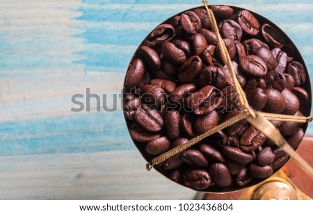 Roasted coffee beans on weight scale over blue wooden background