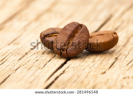 Roasted coffee beans on wooden table - close up shot