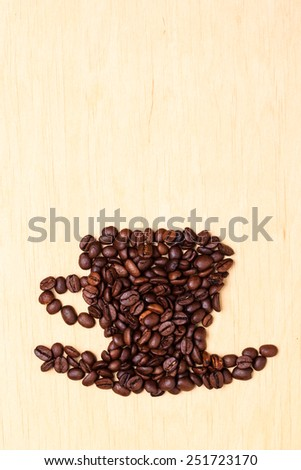 Roasted coffee beans placed in the shape of cup and saucer on wooden surface background, copy space text area