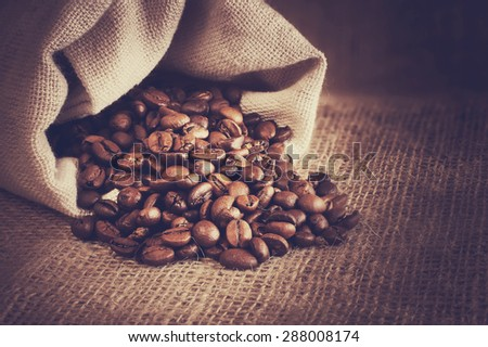 roasted coffee beans spill out of the bag, natural vintage background - stock photo