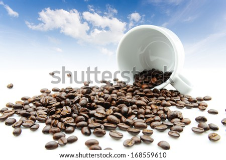 roasted coffee beans splash from coffee cup with blue sky background - stock photo