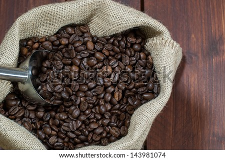 Roasted coffee beans waiting to be ground even in burlap bag on wooden dark table