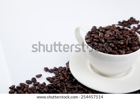 Roasted coffee beans with a cup on white background