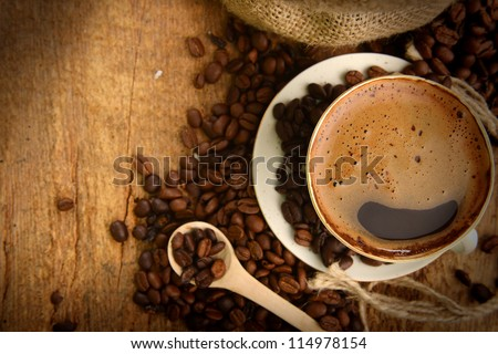 Roasted coffee beans with cup on jute hessian background - stock photo