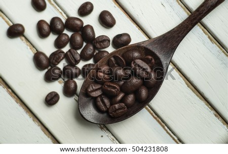 Roasted coffee beans with wooden Spoon on wood