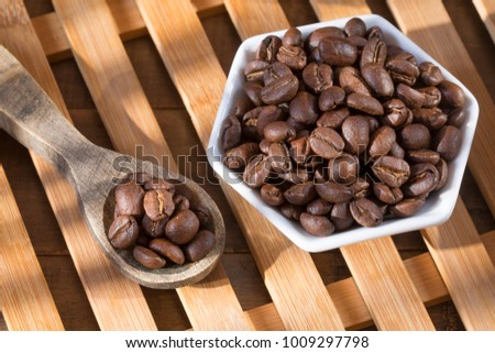 Roasted coffee on the wooden background - Coffea