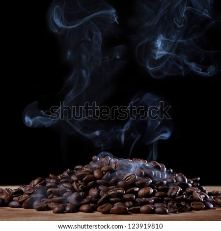 Roasted coffee with smoke on black background