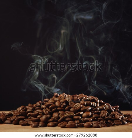 Roasted coffee with smoke on black background - stock photo