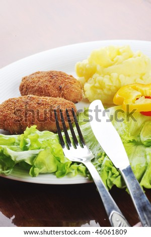 roasted cutlets of pork with potato and  lettuce