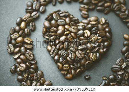 Roasted dark brown coffee beans in a heart shape, can be used as food background