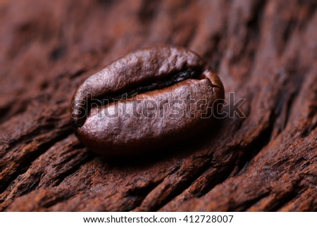 Roasted detailed tasty coffee bean with natural wooden background.