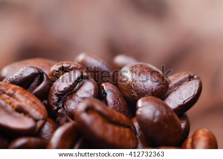 Roasted detailed tasty coffee beans with natural blurry background.
