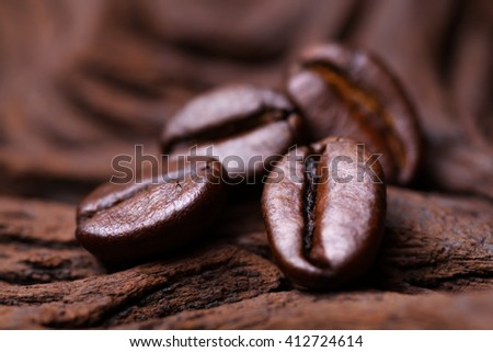Roasted detailed tasty coffee beans with natural wooden background. - stock photo