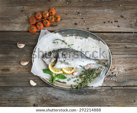 Roasted dorado or sea bream fish with vegetables, herbs and spices on silver tray over rustic wood backdrop, top view, copy space - stock photo