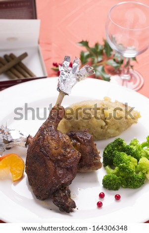 roasted duck leg with braised broccoli and mashed potatoes on decorated plate - stock photo