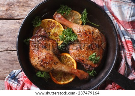 roasted duck legs in a pan with citrus closeup. horizontal view from above  - stock photo