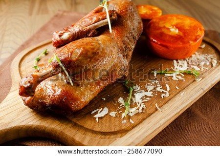 Roasted duck meat with vegetables and orange sauce on a wooden board closeup