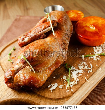 Roasted duck meat with vegetables and orange sauce on a wooden board closeup - stock photo