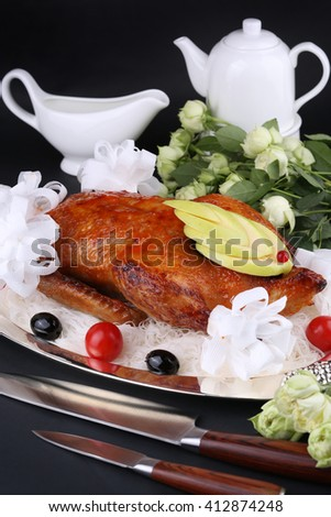 Roasted duck stuffed with apple, garnished cherry tomatoes and olives. White decorated setting. - stock photo
