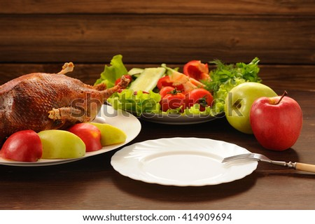 Roasted duck with fresh vegetables and apples and empty plate on wooden table - stock photo