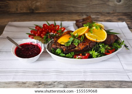 Roasted duck with orange, berry sauce, vegetables and bread  on a wood table - stock photo