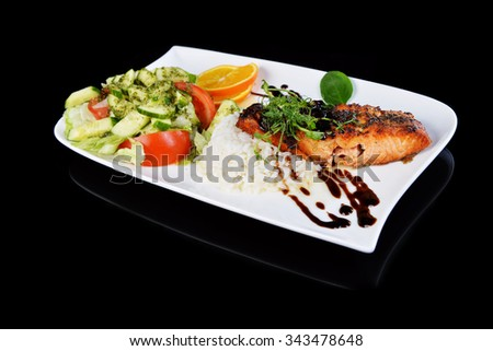 roasted fish,  rice  and vegetables on dish - stock photo