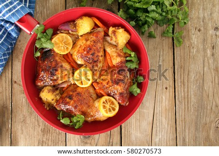Roasted free range organic Chicken skillet dinner with potatoes, carrots, lemon and cilantro.