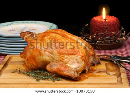 Roasted golden turkey/chicken on carving board in evening setting. - stock photo