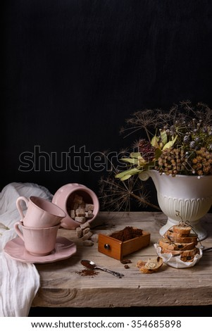 Roasted ground coffee in a wooden box with pink porcelain cups and cookies. Vintage still life on wooden table and copy space. - stock photo