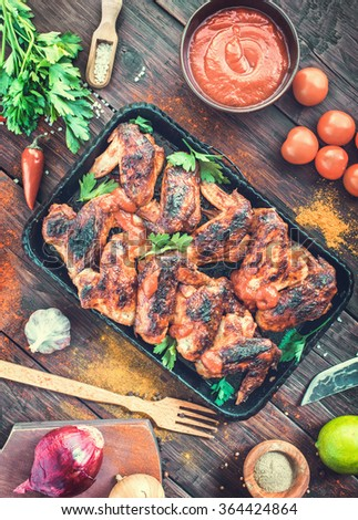 Roasted hot and spicy chicken wings on serving pan. Top view Toned - stock photo