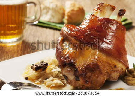 Roasted knuckle of pork with boiled cabbage, bread, horseradish and mustard, served with a mug of cold beer - stock photo